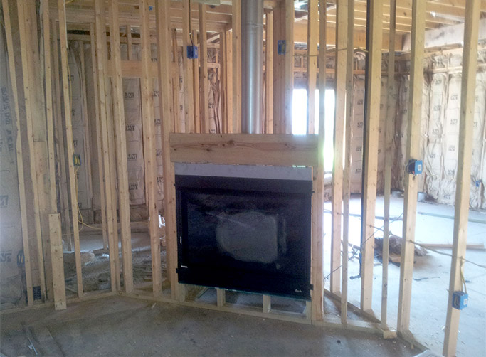In this installation, a Superior DRT3045 direct vent fireplace has been installed into a corner enclosure.  Note the raised platform to allow for a hearth extension and the header that is installed to support the weight of the structure above the fireplace.